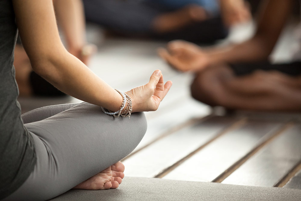 Close up of hands, woman sitting in yoga pose