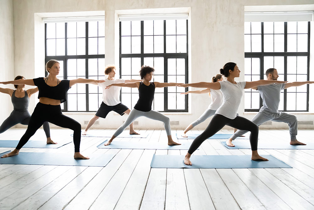 People doing yoga in open room with windows