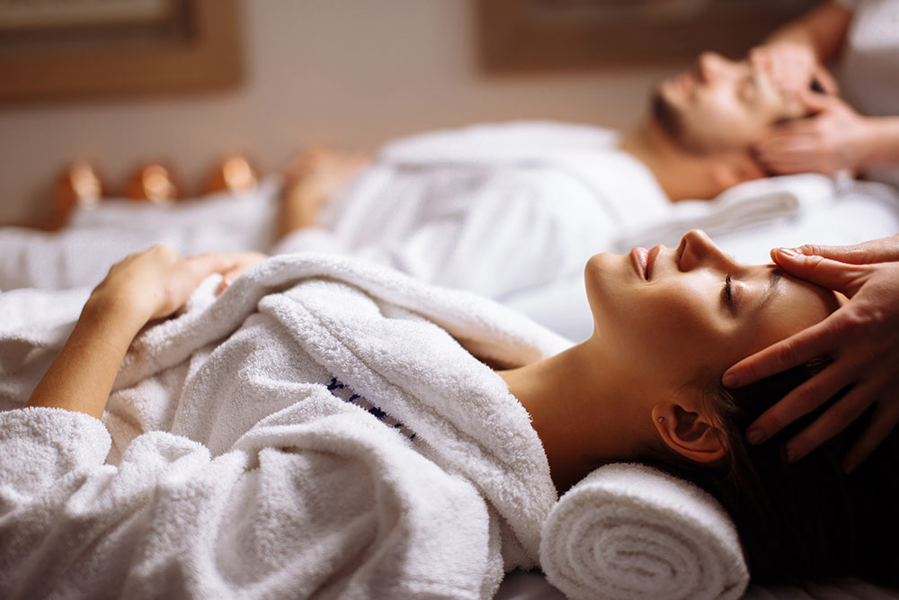 Couple in spa getting massages, relaxing in spa