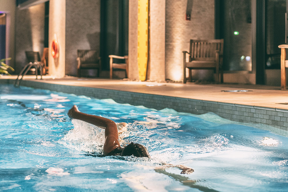 Person swimming in indoor pool