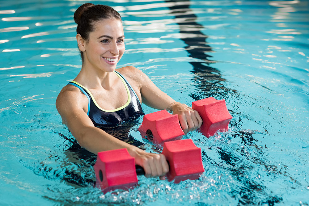 Woman in pool holding foam weights working out and smiling