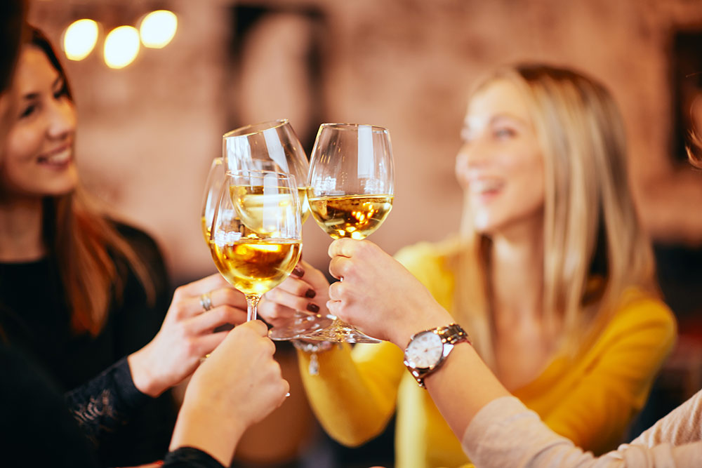 Group of women smiling and cheers with wine glasses