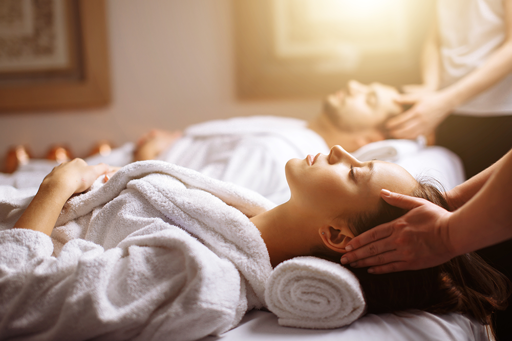 Couple in robes laying on massage table getting a facial massage in spa