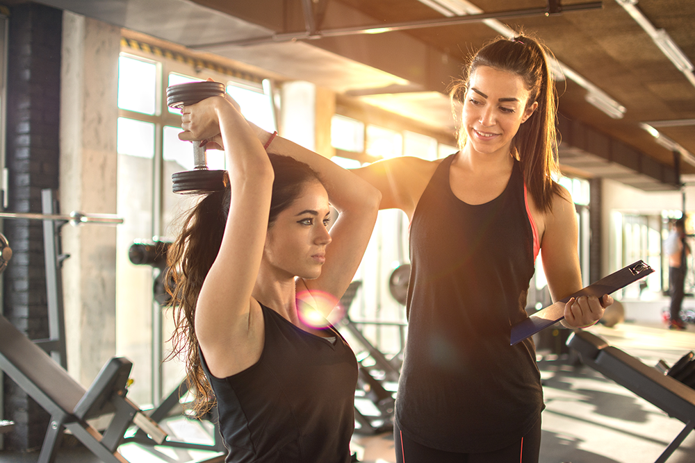 Woman lifting weight with personal trainer next to her guiding her workout