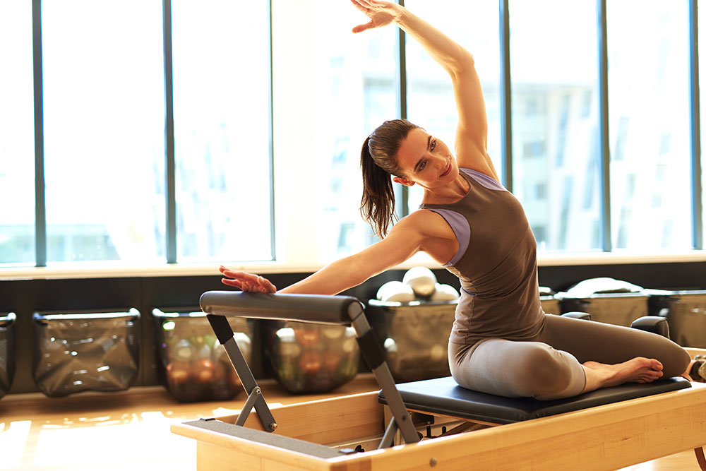 Woman on pilates mat with bar in large room with windows
