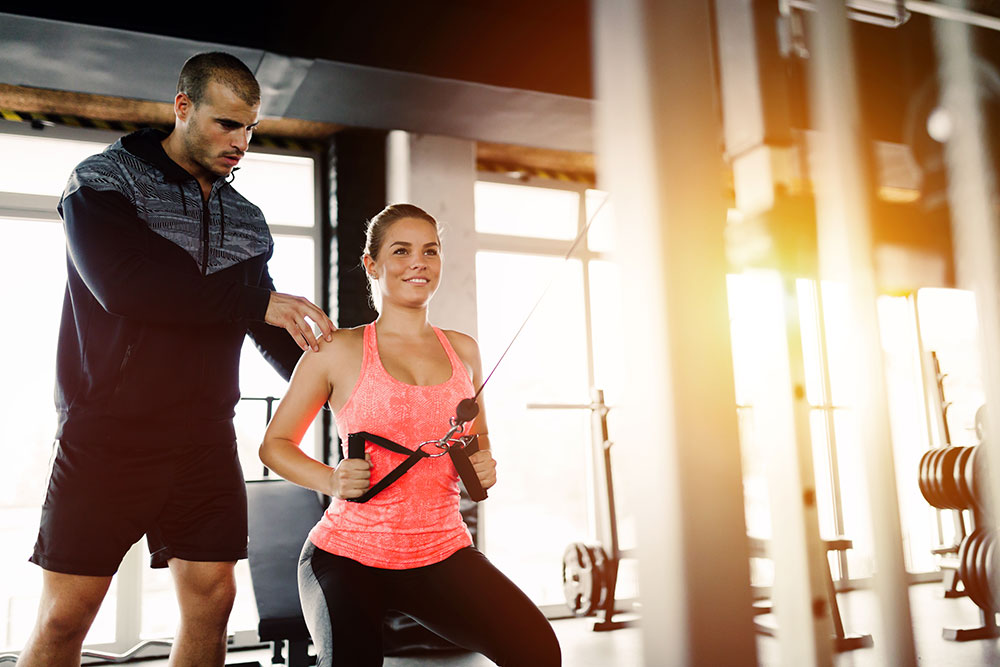 Personal trainer assisting woman with workout in gym