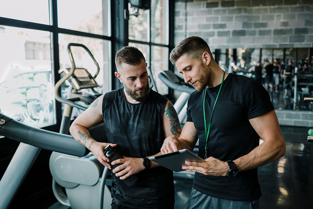 Personal trainer going over workout plans with client in gym
