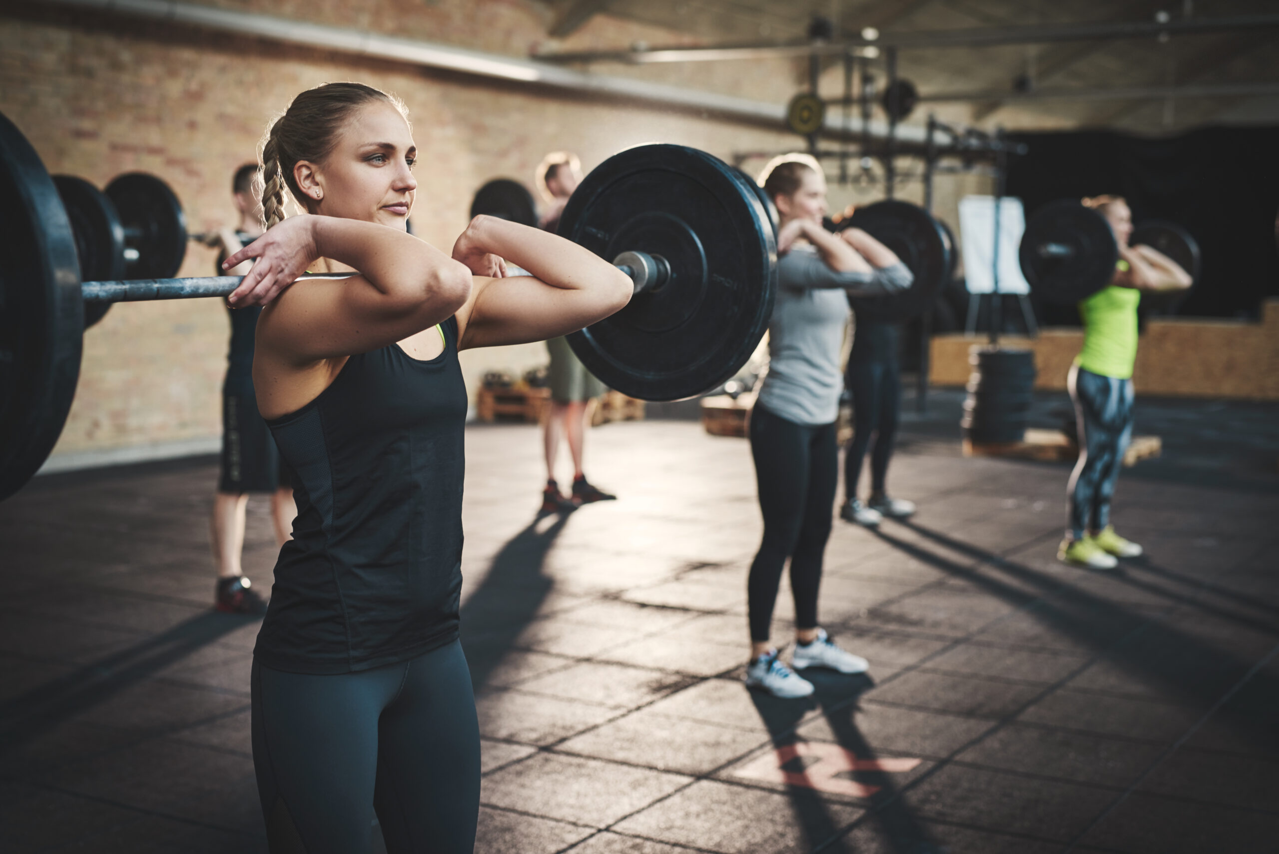 Three women lifting weights during a group fitness class.